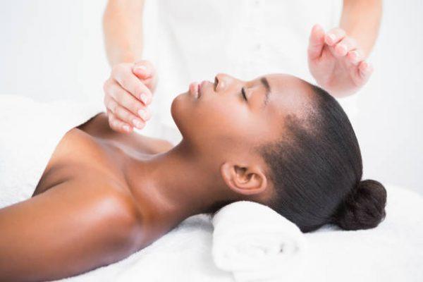 Pretty woman enjoying a reiki technique at the health spa
